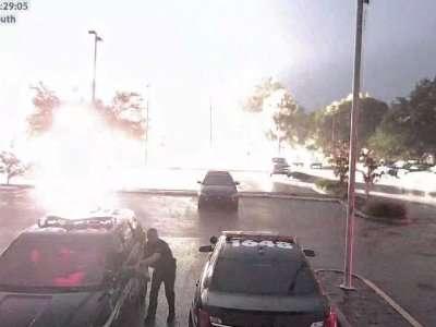 Un ofical de cía de Florida que cargaba su vehículo sufrió un gran impacto cuando un rayo cayó en el estacionamiento detrás de él. Foto: AP