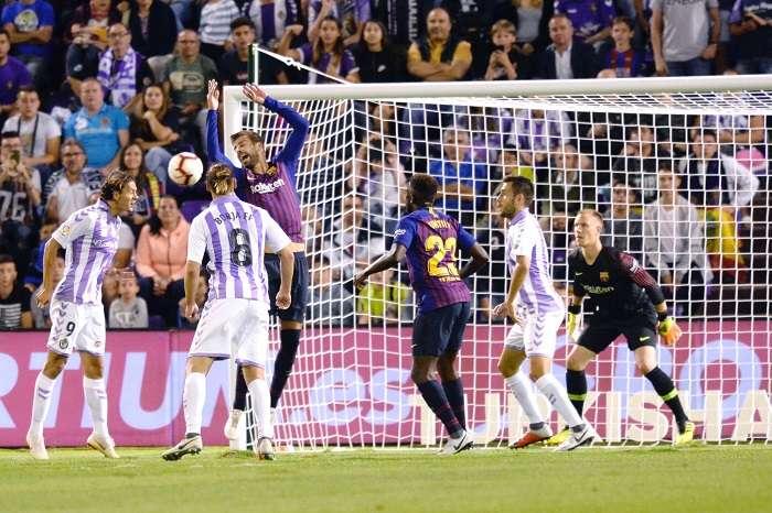 El delantero turco del Real Valladolid, Enes Unal (i), remata ante el defensa del FC Barcelona, Gerard Piqué, durante el encuentro correspondiente a la segunda jornada de primera división disputado esta noche en el estadio José Zorrilla. /EFE