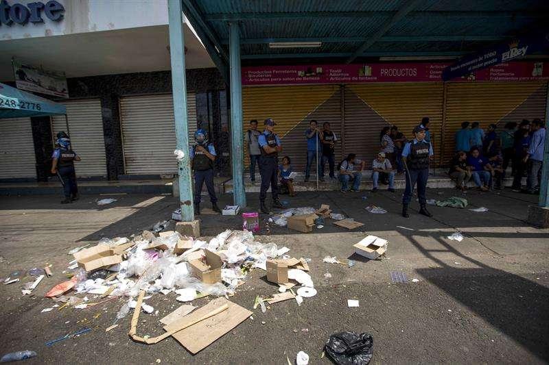 Comerciantes y miembros de la Policía Nacional fueron registrados este viernes al vigilar varios negocios después de un intento de saqueo en el Mercado Oriental, en Managua (Nicaragua). EFE