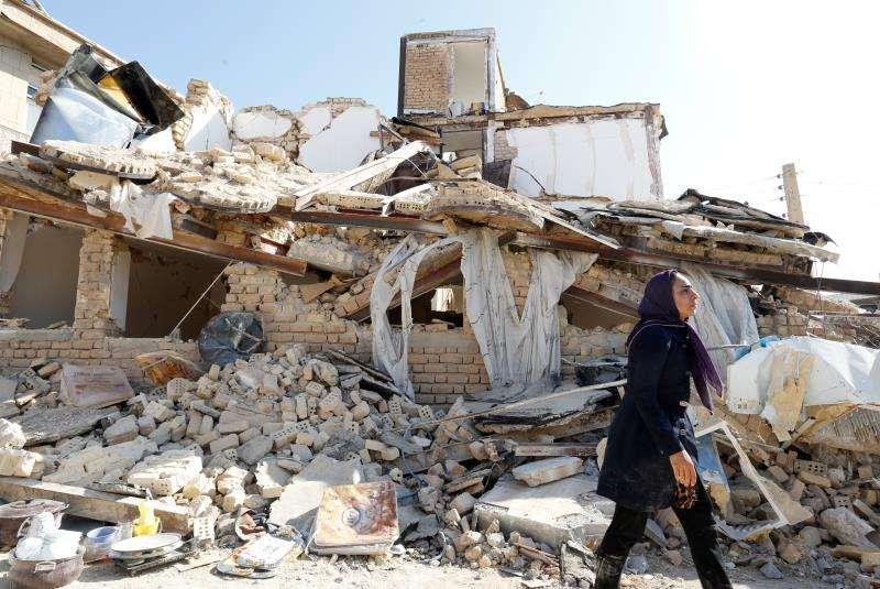 Una mujer iraní pasa delante una casa derrumbada en la localidad de Sare Pole-Zahab, provincia de Kermanshah (Irán) en el pasad0 noviembre de 2017. EFE/Archivo