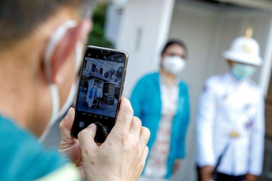 Un turista chino posa para una foto con un guardia real tailandés (R), ambos con máscaras protectoras en el Gran Palacio de Bangkok, Tailandia. EFE