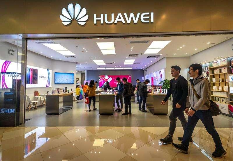 Personas caminan frente a la tienda de Huawei en Guangzhou (China). EFE