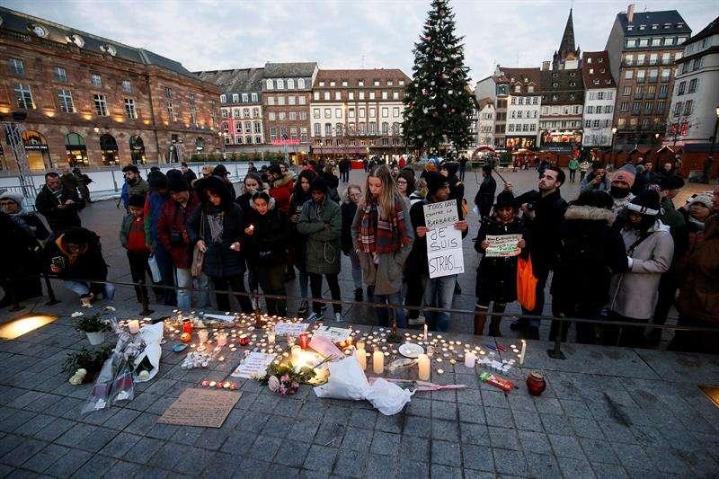 Ciudadanos encienden velas y escriben mensajes hoy, 12 de diciembre de 2018, en el lugar donde falleció una de las víctimas en el atentado en Estrasburgo (Francia). EFE