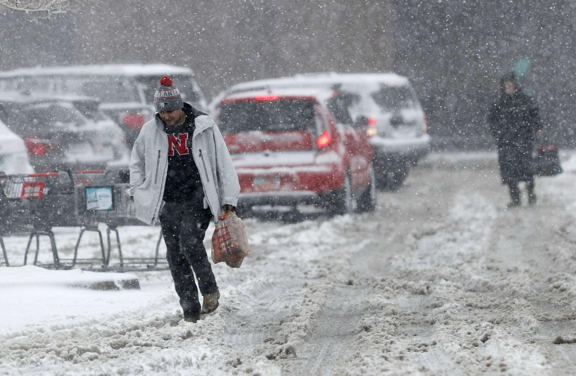 Los compradores luchan para dirigirse a sus vehículos fuera de una tienda de comestibles mientras una tormenta a finales de invierno arrastra vientos huracanados y vientos de nieve en la montaña. AP