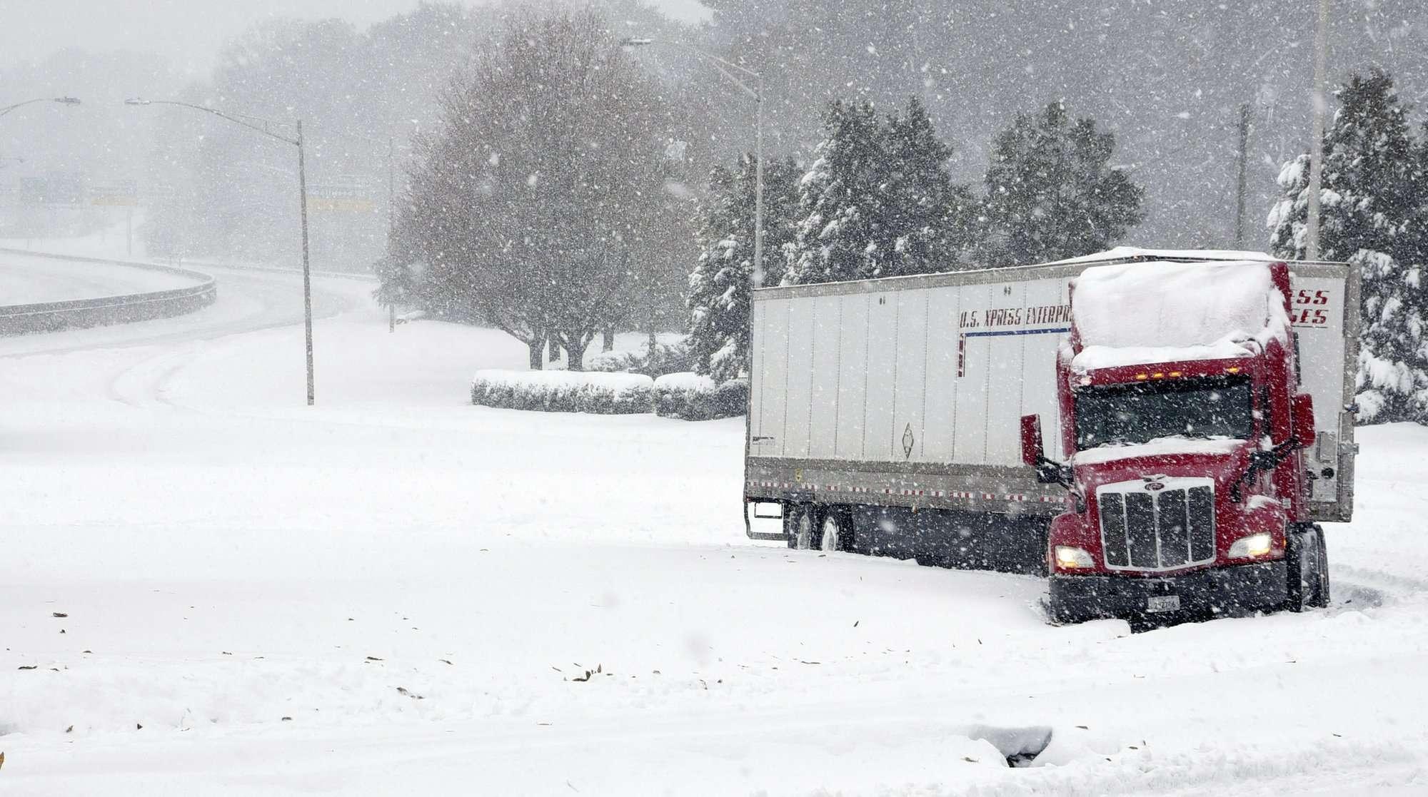 Un remolque de tractor está atascado en una rampa de salida de Business I-40 hacia Stratford Road, US 158, mientras cae nieve en Winston-Salem, NC (Walt Unks / Winston-Salem Journal a través de AP)