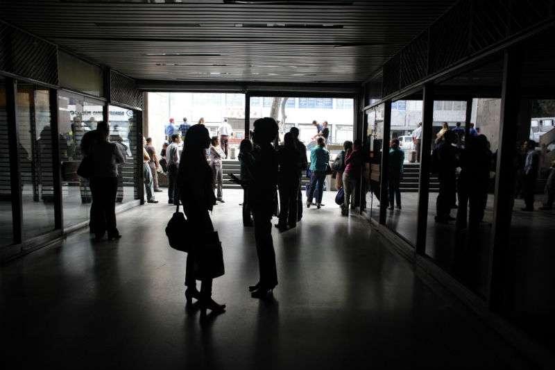 Empleados permanecen en la entrada principal de un edificio de oficinas durante un apagón en Caracas, Venezuela. Foto: AP