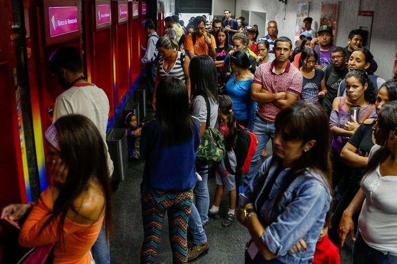 Personas hacen fila para retirar dinero en un cajero automático este miércoles, en Caracas (Venezuela). EFE