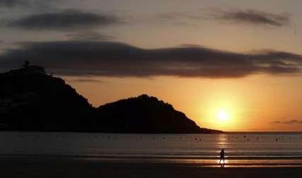 Donostiarras y visitantes disfrutan del atardecer en la playa de la Concha de San Sebastián. /  Foto: EFE