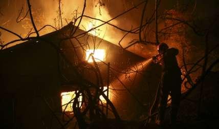 Un bombero intenta extinguir un incendio en una casa durante un incendio forestal en el pueblo de Kalamos, al norte de Atenas. / Foto: AP