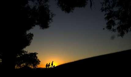 La gente camina sobre una colina mientras el sol se pone en un día de verano en el parque Tio Pio en Madrid.  /  Foto: AP
