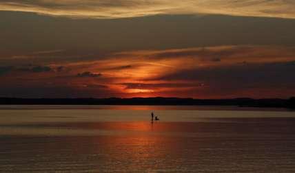 Una pareja hace su camino en un tablero de paleta durante la puesta de sol en el lago 'Chiemsee' en Chieming, Alemania.  /  Foto: AP