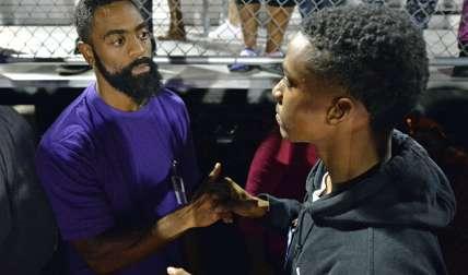 Un compañero de clase de Trinity Gay ofrece sus condolencias a su padre, Tyson Gay. Foto AP
