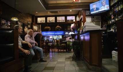 Dos hombres observan el tercer y último debate de los candidatos a la presidencia de EE.UU. entre el republicano Donald Trump y la demócrata Hillary Clinton , en Astoria (EE.UU.).  /  Foto: EFE