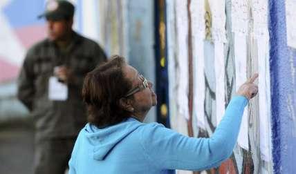 Una mujer busca su mesa de votación para participar de los comicios en Venezuela.  /  EFE