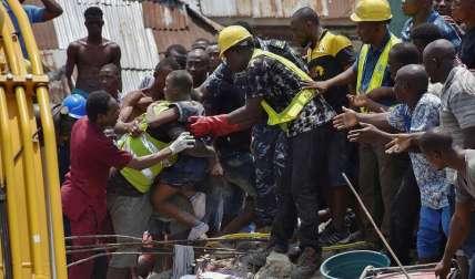 Operarios rescatan a un niño entre los escombros tras derrumbarse un edificio este miércoles en Lagos, Nigeria. EFE