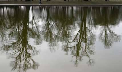 Los árboles se reflejan en la piscina entre el Monumento Nacional de la Segunda Guerra Mundial y el Lincoln Memorial en Washington, mientras la gente camina por el borde. / Foto de AP