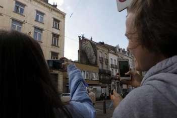 Dos personas fotografían uno de los grafitis de alto contenido sexual que han aparecido esta semana en Bruselas.  /  Foto: EFE